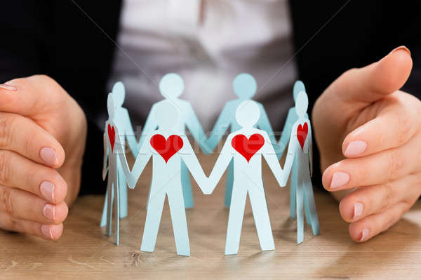 Hand Protecting Circle Of Paper Cut-out Figures Stock photo © AndreyPopov