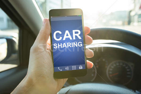 Driver Holding Smart Phone With Car Sharing App On Screen Stock photo © AndreyPopov
