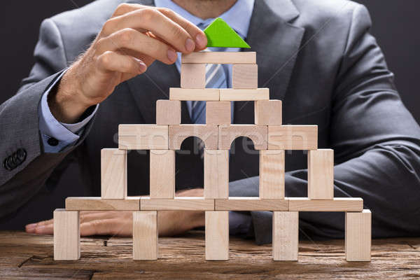 Businessman Making Building With Wooden Blocks Stock photo © AndreyPopov