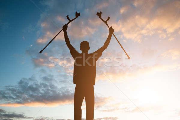 Sziluett mozgássérült férfi mankók tart drámai Stock fotó © AndreyPopov