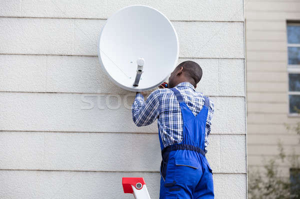 Man In Uniform Fitting TV Satellite Dish Stock photo © AndreyPopov