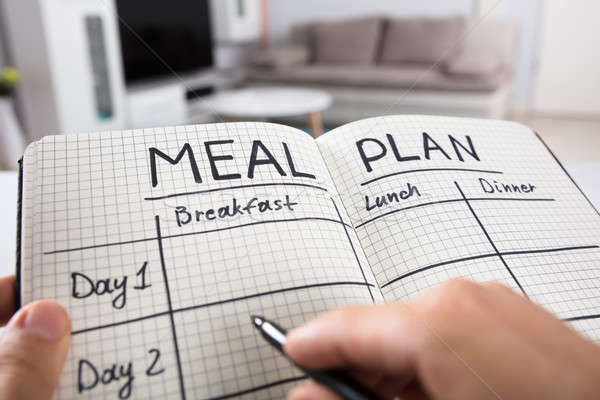 Human Hand Filling Meal Plan In Notebook Stock photo © AndreyPopov