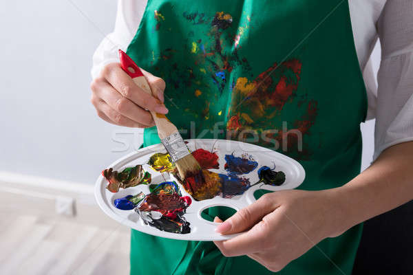 Stock photo: An Artist Holding Paint Palette And Paintbrush