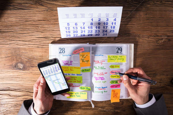Stock photo: Businessperson With Mobile Phone Writing Schedule In Diary