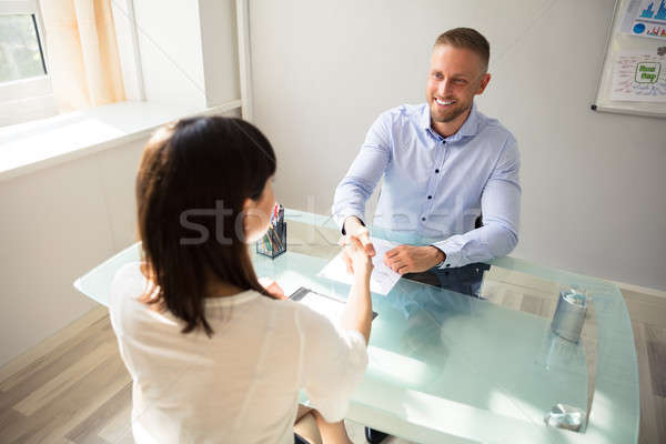 Smiling Young Businessman Shaking Hand With Female Candidate Stock photo © AndreyPopov