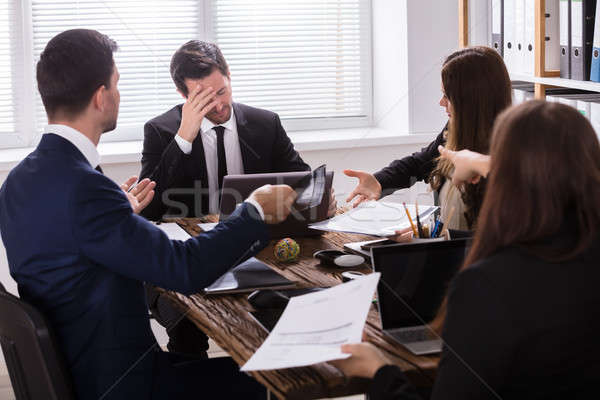 Businesspeople Blaming Depressed Male Colleague Stock photo © AndreyPopov