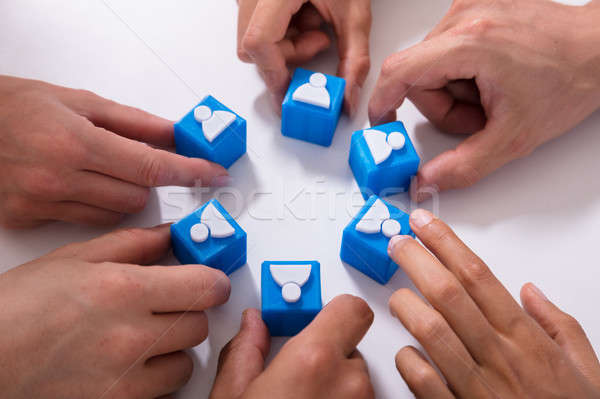 Businesspeople Holding Cubic Blocks With Human Figures Stock photo © AndreyPopov