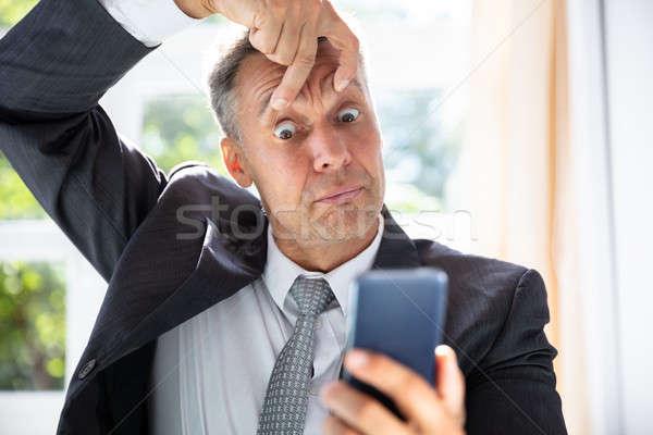 Przerażony biznesmen patrząc telefonu komórkowego ekranu Zdjęcia stock © AndreyPopov