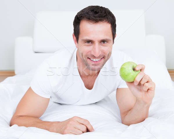 Young Man Lying On Bed Holding Green Apple Stock photo © AndreyPopov