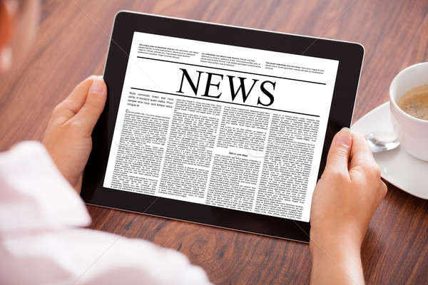 Woman Looking At News Article Stock photo © AndreyPopov