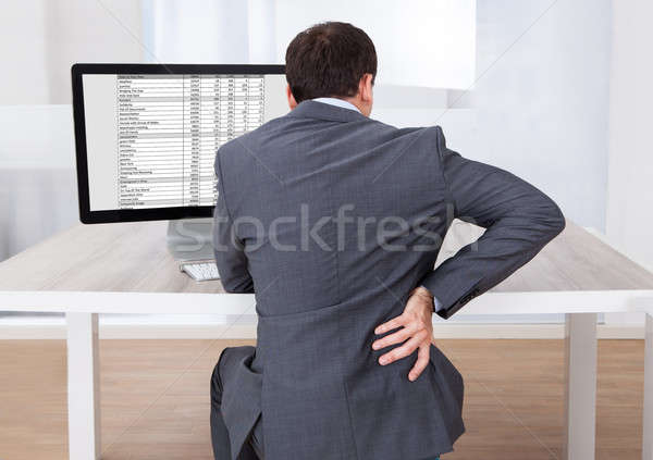 Businessman Suffering From Backache While Sitting At Desk Stock photo © AndreyPopov
