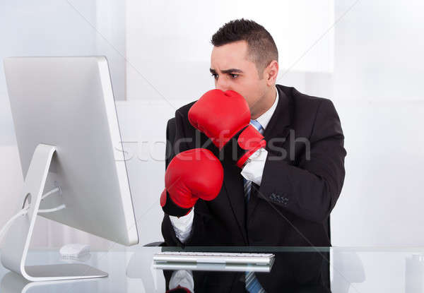 Stock photo: Scared Businessman With Boxing Gloves Looking At Computer