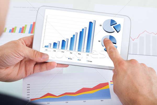 Businessman Comparing Graphs On Digital Tablet At Office Desk Stock photo © AndreyPopov
