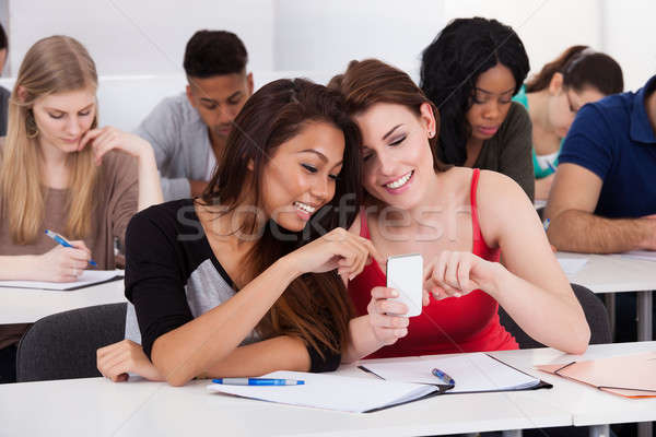Stock photo: Happy female college students using mobile phone together