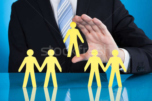 Businessman Holding Paper People Representing Recruitment Stock photo © AndreyPopov