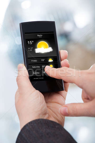 Businesswoman Checking Weather Forecast On Smartphone Stock photo © AndreyPopov