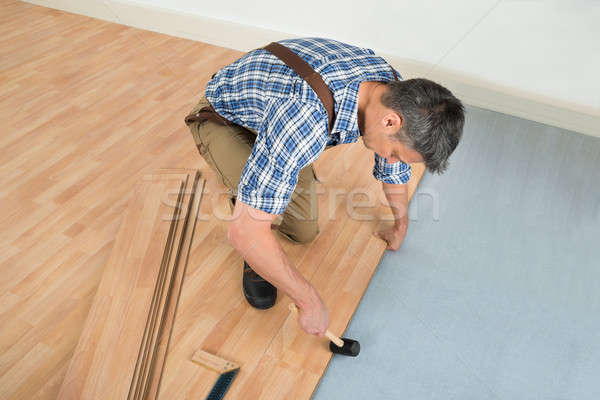 Worker Assembling New Laminate Floor Stock photo © AndreyPopov