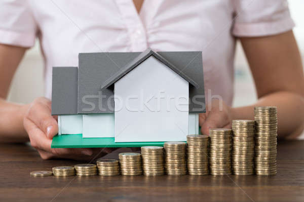Businesswoman With House Model And Stack Of Coins Stock photo © AndreyPopov