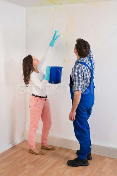 Woman Showing Water Leaking From Ceiling To Maintenance Guy Stock photo © AndreyPopov