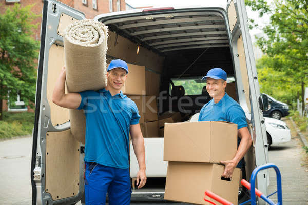 Workers Carrying Carpet And Cardboard Boxes Stock photo © AndreyPopov