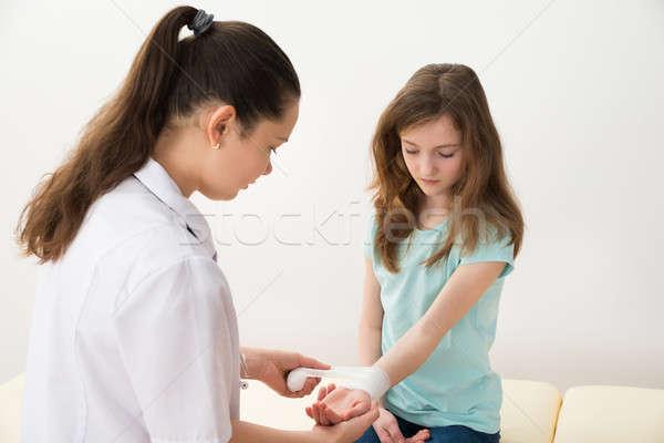 Doctor Bandaging Hands Of Girl Child Stock photo © AndreyPopov