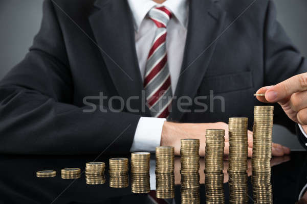 Businessman Placing Coin Over Stack Of Coins Stock photo © AndreyPopov