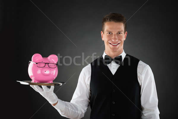 Butler Holding Tray With Piggybank Stock photo © AndreyPopov