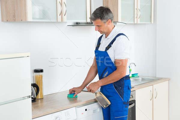 Férfi gondnok takarítás konyhapult mosószer spray Stock fotó © AndreyPopov