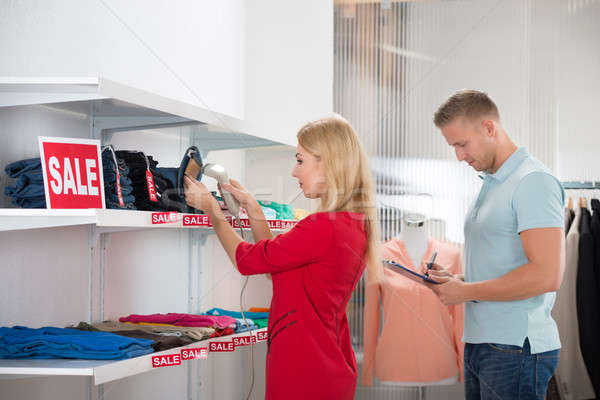 Woman Scanning Tag While Colleague Writing On Clipboard Stock photo © AndreyPopov