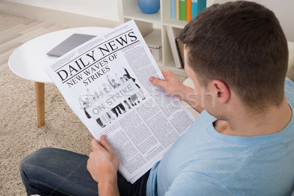 Man Reading News On Newspaper At Home Stock photo © AndreyPopov