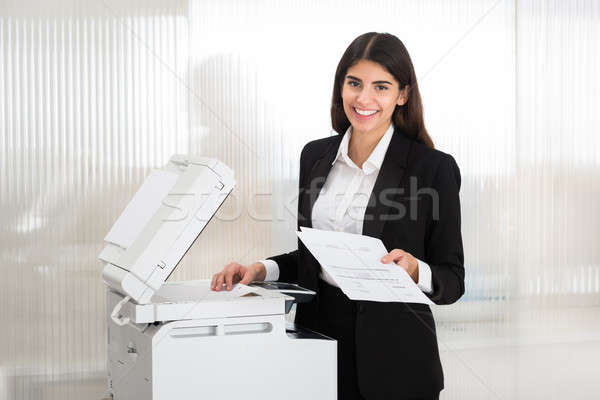 Businesswoman Using Photocopy Machine In Office Stock photo © AndreyPopov