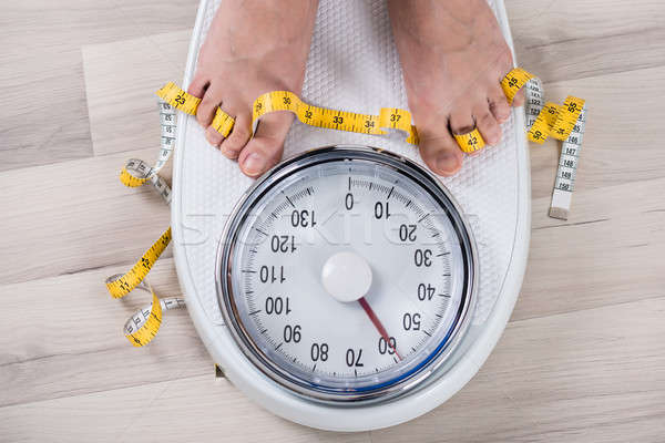 Person Leg On Weighing Scale Stock photo © AndreyPopov