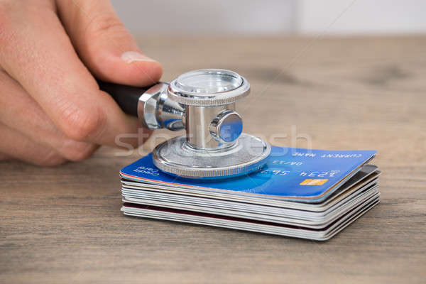 Person Hand Holding Medical Stethoscope On Credit Card Stack Stock photo © AndreyPopov
