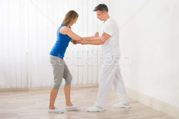 Physiotherapist Assisting Woman For Exercising Stock photo © AndreyPopov