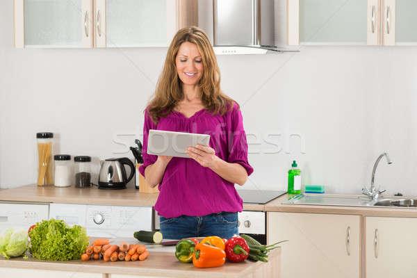 Mujer mirando receta digital tableta hortalizas Foto stock © AndreyPopov