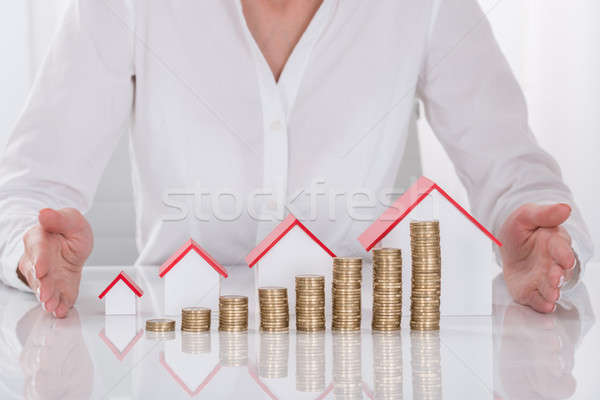 Businesswoman Hands Protecting Coins And House Models Stock photo © AndreyPopov