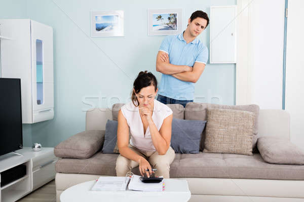 Suspicious Man Looking At Bills From Behind His Wife Stock photo © AndreyPopov