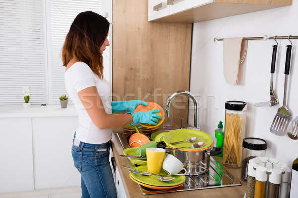 Unhappy Woman Washing Utensil In The Kitchen Stock photo © AndreyPopov