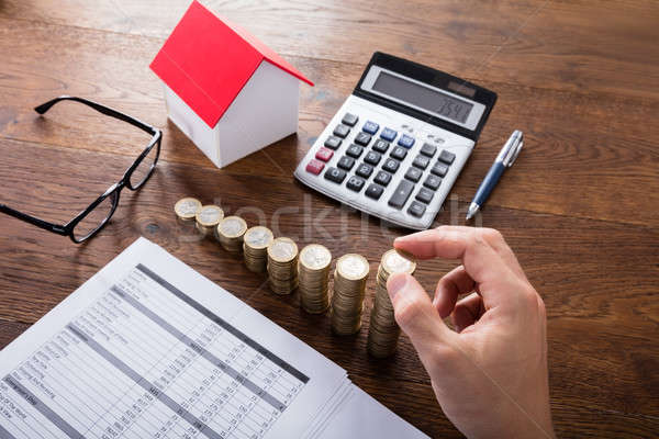 Person Stacking Coins On Wooden Desk Stock photo © AndreyPopov