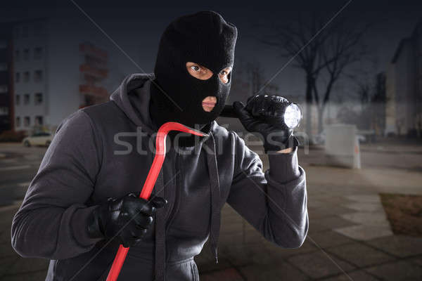 Burglar With A Crowbar And A Flashlight Stock photo © AndreyPopov