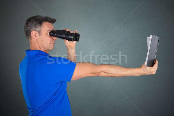 Man With Hyperopia Eye Disorder Reading A Book Using Binocular Stock photo © AndreyPopov
