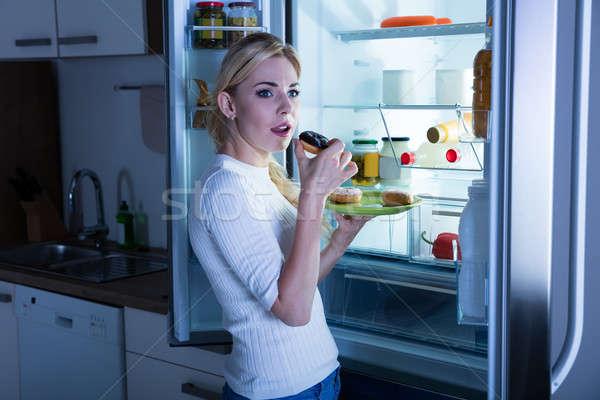 Woman Eating Donut Secretly From Fridge Stock photo © AndreyPopov
