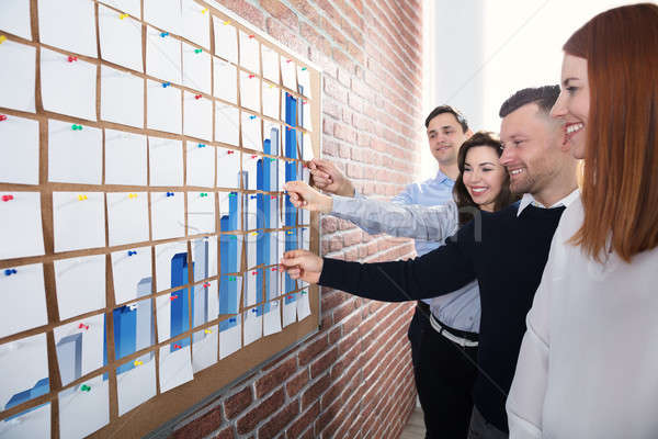 Wykres przyczepny zauważa ludzi biznesu patrząc biuro Zdjęcia stock © AndreyPopov