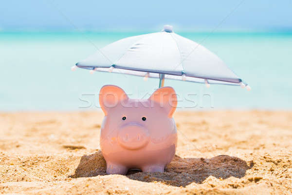 Piggy Bank Under The Parasol At Beach Stock photo © AndreyPopov