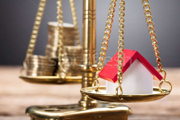 Model Home And Coins On Golden Weighing Scale Stock photo © AndreyPopov