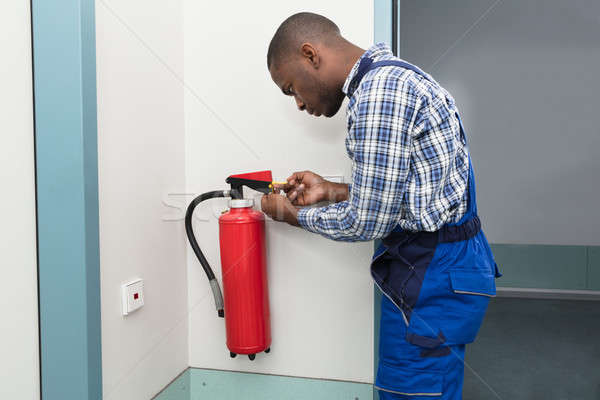 Male Professional Checking A Fire Extinguisher Stock photo © AndreyPopov