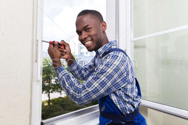 Handyman In Uniform Fixing Glass Window Stock photo © AndreyPopov