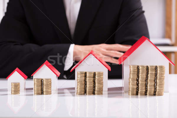 Coins And Different Sizes House Model Front Of Businessman Stock photo © AndreyPopov