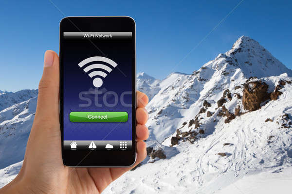 Hand Holding Mobile Phone With Wi-fi Signal Stock photo © AndreyPopov