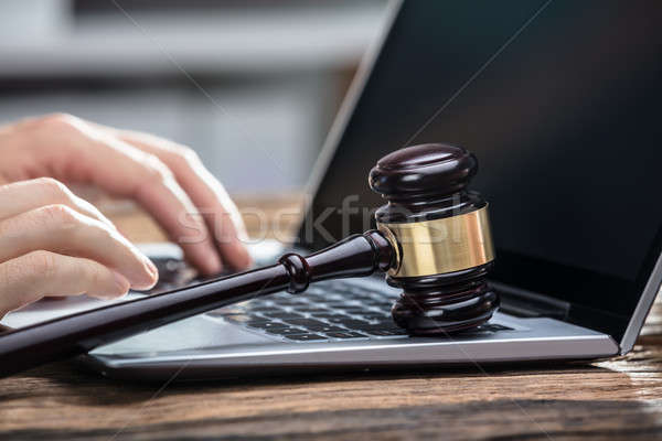 Businessperson's Hand Using Laptop On Wooden Desk Stock photo © AndreyPopov